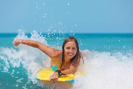 Joyful ung flicka - nybörjare surfare med bodyboard har kul på små havsvågor. Aktiv familj livsstil, människor utomhus vattensporter lektioner och simning aktivitet på surfa läger sommarlov med barn Stockfoto