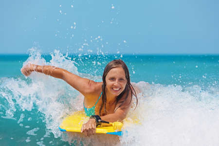 Joyful young girl - beginner surfer with bodyboard has fun on small sea waves. Active family lifestyle, people outdoor water sport lessons and swimming activity on surf camp summer vacation with child