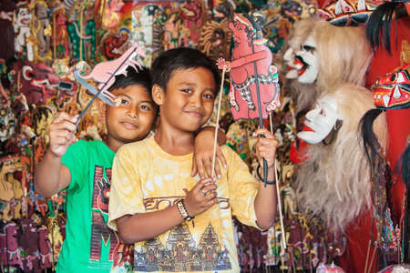 puppeteer: BALI ISLAND, INDONESIA - JULY 11, 2015: Smiley balinese children have fun and play with characters of traditional shadow puppets - wayang kulit. Arts, crafts and culture festivals of Indonesian people