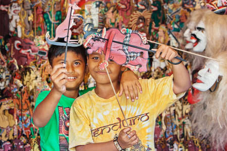 indonesian: BALI ISLAND, INDONESIA - JULY 11, 2015: Smiley balinese children have fun and play with characters of traditional shadow puppets - wayang kulit. Arts, crafts and culture festivals of Indonesian people