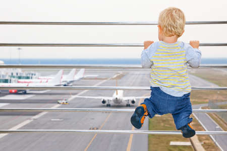Little baby boy waiting boarding to flight in airport transit hall and looking through the window at airplane near departure gate. Active lifestyle, travel by air with child on family summer vacation.