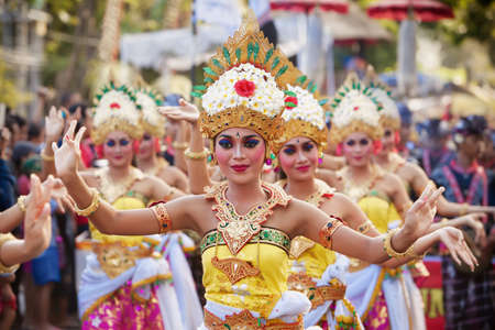 BALI, INDONESIA - JUNE 13, 2015: Beautiful women group dressed in colorful sarongs - Balinese style female dancer costume, dancing traditional temple dance Legong at Bali Art and Culture Festival show 新聞圖片