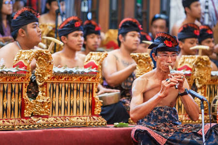 BALI, INDONESIEN - 21 JUNI 2015: Gamla musikerman av traditionell Gamelan orkester klädd i balinesisk manlig kostym som spelar etnisk musik på bambuflöjt Suling på konst och kulturfestival.