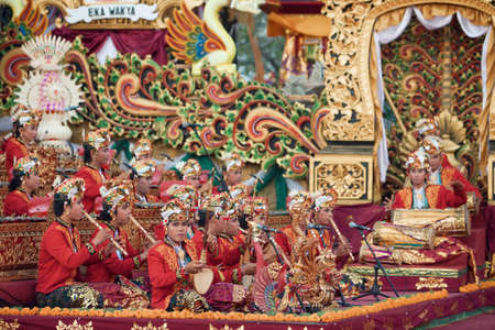 male costume: BALI, INDONESIA - JUNE 21, 2015: Group of young musician men of Gamelan orchestra dressed in Balinese style male costume playing ethnic music Kabyar at Art and Culture Festival. Editorial