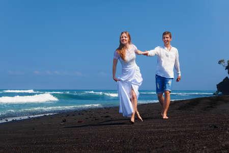 Lycklig nygift familj på smekmånad semester - precis gift älskande par kör med kul på havet svart sandstrand. Aktiv livsstil, folk bröllop utomhus aktivitet på semester på tropisk ö.