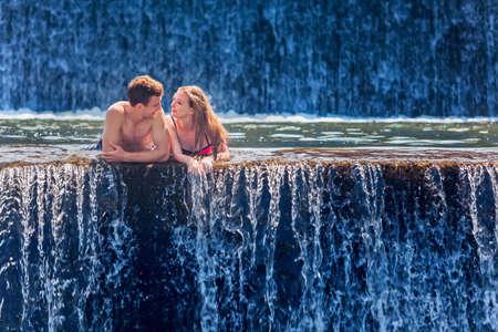 luna de miel: familia feliz de vacaciones de luna de miel - apenas casado natación pareja amorosa con la diversión en la piscina cascada natural. estilo de vida activo, las personas actividad al aire libre en los viajes de vacaciones de verano en la isla tropical de Bali