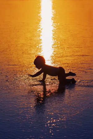 shadow silhouette: Black shadow silhouette of playful baby running on wet gold sunset sand to sea surf to swim in beach wave. Family travel lifestyle background, water outdoor activity on Bali summer vacation with child Stock Photo