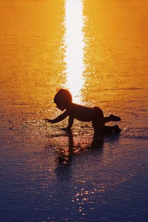 silueta niño: Sombra de la silueta del negro del bebé juguetona que se ejecuta en la arena mojada puesta de sol de oro a la resaca del mar a nadar en la onda playa. Vida de la familia antecedentes de viajes, agua actividad al aire libre en Bali vacaciones de verano con niños Foto de archivo