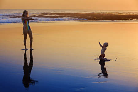 black shadows: Silhouette with black shadows of mother with baby running on wet gold sunset sand to sea surf to swim in beach wave. Family travel background, water outdoor activity on Bali summer vacation with child Stock Photo