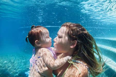 niños sonriendo: Familia feliz - Madre del beso de la niña de submarinismo abajo con la diversión en piscina de la playa. estilo de vida saludable, los padres activos, la actividad del deporte acuático de personas y clases de natación bajo el agua en las vacaciones de verano con el niño. Foto de archivo