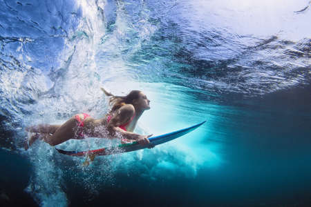swimming: Young girl in bikini - surfer with surf board dive underwater with fun under big ocean wave. Family lifestyle, people water sport lessons and beach swimming activity on summer vacation with child
