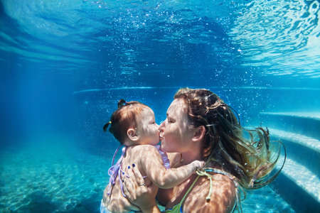 Happy family - mother kiss baby girl dive down with fun in beach pool. Healthy lifestyle, active parents, people water sport activity and underwater swimming lessons on summer vacation with child. Banco de Imagens