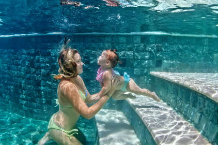hand hold: Happy family - mother hold in hands baby girl and dive down with fun in beach pool, active parents lifestyle, people water sport activity and underwater swimming lesson on summer vacation with child.