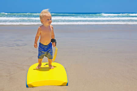 bodyboarder: Little baby boy - young surfer with bodyboard has fun on sea sand beach with waves. Family lifestyle, people outdoor water sport lessons and swimming activity on summer surf camp vacation with child. Stock Photo