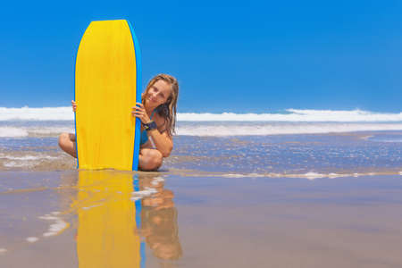 Bonne fille - jeune surfeur avec bodyboard a du plaisir sur la plage de sable de la mer avec des vagues. mode de vie de la famille, cours de sport gens de l'eau, l'activité de natation en été surf camp de vacances avec un enfant dans l'île de l'océan.