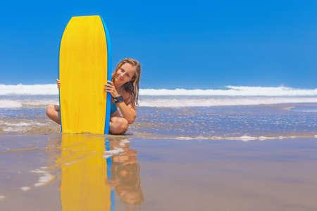 Gelukkig meisje - jonge surfer met bodyboard heeft plezier op zee zand strand met golven. Familie lifestyle, mensen water sportlessen, zwemmen activiteit op summer camp vakantie met kind in oceaan eiland. Stockfoto