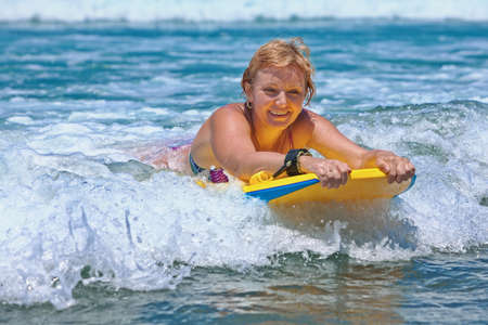Joyful middle age woman - surfer with bodyboard surfing with fun on small sea waves. Active family lifestyle, people outdoor water sport lesson and swimming activity on summer vacation in ocean island.