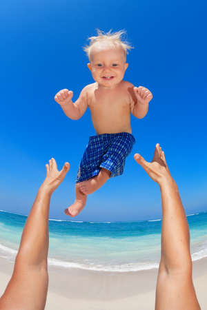 Family swimming fun on white sand sea beach and blue sky - father hands tossing up baby boy into mid air and catching. Child outdoor activity, active lifestyle on summer vacation in tropical island.