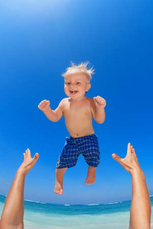 Family swimming fun on white sand sea beach and blue sky - father hands tossing up baby boy into mid air and catching. Child outdoor activity, active lifestyle on summer vacation in tropical island. Banque d'images