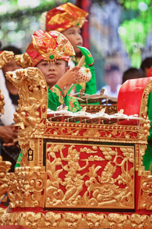 gamelan: BALI, INDONESIA - JULY 11, 2015: Little child - musician of Gamelan orchestra in Balinese people costume playing ethnic ritual music on traditional percussion instrument at Art and Culture Festival.