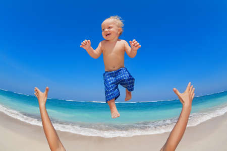 mid air: Family swimming fun on white sand sea beach and blue sky - father hands tossing up baby boy into mid air and catching. Child outdoor activity, active lifestyle on summer vacation in tropical island. Stock Photo