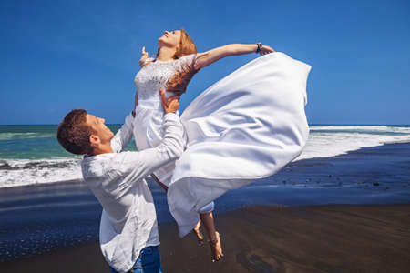 honeymoon: Happy newlywed family has fun on honeymoon holidays on sea black sand beach - married loving man tossing up high in air girl in white flying dress. People activity on summer vacation on island Bali.