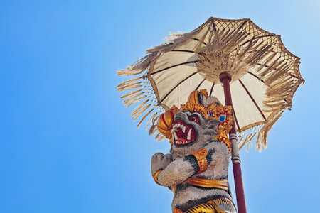 travel backgrounds: Monkey Hanuman - traditional protective spirit and Bali island symbol under ceremonial umbrella in front of temple. Arts, religion and culture festivals of Indonesian people. Asian travel backgrounds.