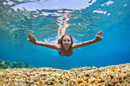 underwater woman: Happy beautiful girl - young woman dive underwater with fun over coral reef in sea pool. Healthy active lifestyle, people water sport outdoor activity and swimming lessons on beach summer holidays.