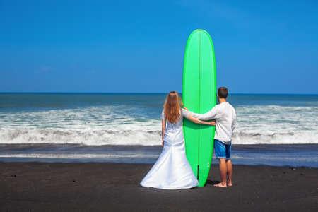 luna de miel: la familia del recién casado en las vacaciones de luna de miel - pareja de recién casados ??de pie con tabla de surf en la playa de arena negro y mirar hacia adelante a la mar. estilo de vida activo, las personas actividades al aire libre del deporte de agua en las vacaciones de verano. Foto de archivo