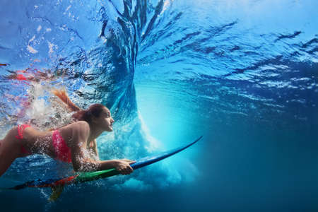 Young girl in bikini - surfer with surf board dive underwater under big ocean wave Family lifestyle, people water sport adventure camp and beach extreme swimming activity on summer vacation with child Standard-Bild