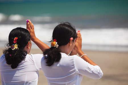 Twee Aziatische vrouwen met biddende handen op de oceaan strand bij ceremonie Melasti vóór Balinese Nieuwjaar en de stilte dag Nyepi. Vakanties, festivals, rituelen, kunst, cultuur van de Indonesische bevolking en het eiland van Bali.