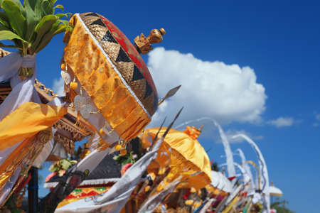 Traditional ceremonial umbrellas and flags on beach at ceremony Melasti before Balinese New Year and silence day Nyepi. Holidays, festivals, rituals, art, culture of Indonesian people and Bali island.