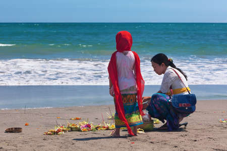 indonesia girl: BALI, INDONESIA - MARCH 18, 2015: Asian woman and girl make traditional offering Canang sari for spirits of Bali on ocean beach during ceremony Melasti before Balinese New Year and silence day Nyepi.