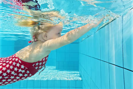 kids club: Child swimming lesson - girl learning to dive underwater in pool. Healthy active family lifestyle, physical exercise and water sports activity with parents on summer holiday with kid in aquatic center