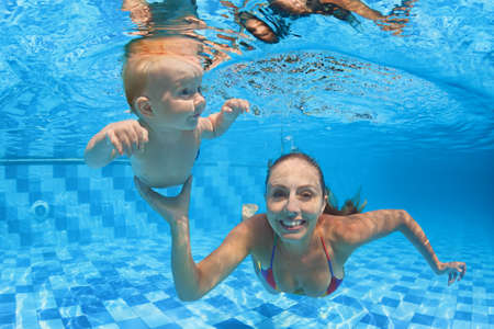 Barn simundervisning - baby med mamma l�ra sig att dyka under vattnet i poolen friska aktiv familj livsstil, motion och vattensport aktivitet med f�r�lder p� sommarsemester i gymmet