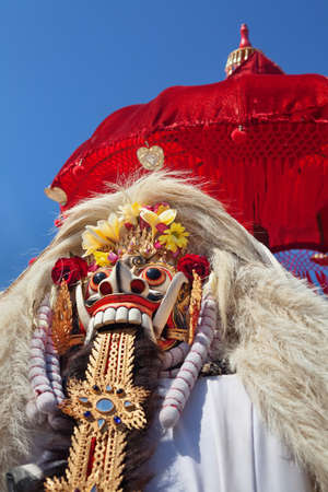 Rangda Mask under red umbrella in temple - traditional spirit of Bali at ceremony Melasti before Balinese New Year and silence day Nyepi Holidays, festivals, rituals, art, culture of Indonesian people Stock Photo