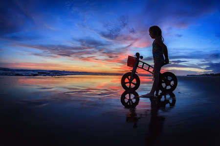 bali beach: Black silhouette of little child - run bike rider stand on wet sand beach, look at sea surf and colourful sunset sky. Family travel lifestyle background, outdoor fun activity on Bali summer vacation.
