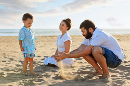 Happy family - mother, father and small baby son sit on sunset sea beach and play with sand slipping through man hand fingers. Active parents and people outdoor activity on summer vacations with child