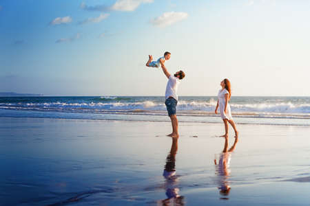 Happy family - père, mère, fils de bébé marcher avec plaisir le long bord de mer coucher de soleil surfer sur plage de sable noir. Les parents actifs et les gens l'activité en plein air sur les vacances d'été avec les enfants sur l'île de Bali Banque d'images