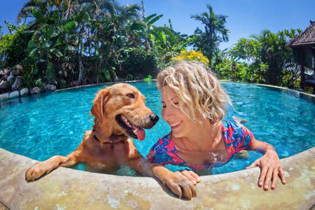 Funny portrait of smiley woman playing with fun and training golden retriever puppy in outdoor swimming pool. Popular dog like companion, outdoor activity and game with family pet on summer holiday.