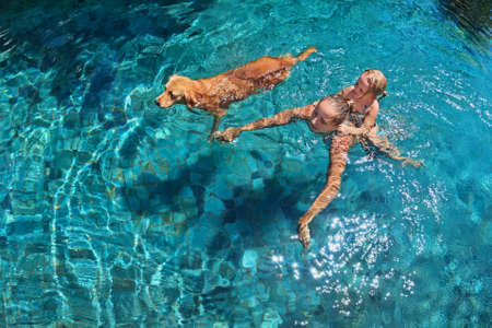 Mother with little child on back play with fun and train golden labrador retriever puppy in swimming pool. Popular dog like companion, outdoor activity and funny game with family pet on summer holiday