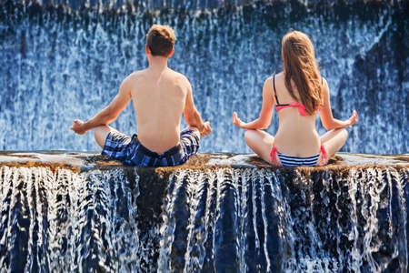 luna de miel: familia feliz de vacaciones de luna de miel - pareja de reci�n casados ??en posici�n de loto de yoga despu�s de nadar en la piscina cascada. estilo de vida activo, las personas actividad al aire libre en los viajes de vacaciones de verano en la zona tropical de Bali.
