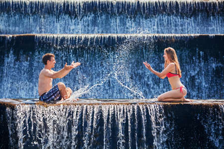 active: Happy family on honeymoon holidays - just married loving couple swimming and splashing with fun in waterfall pool. Active lifestyle, people outdoor travel activity on summer vacation on tropical Bali.
