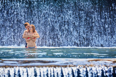 water flowing: Happy family on honeymoon holidays - just married couple embracing and swimming with fun in waterfall pool. Active lifestyle, people outdoor travel activity on summer vacation on tropical Bali island.