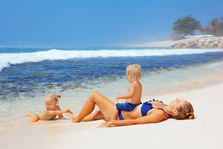 Happy family - mother, baby son and daughter lying on sand beach and look at sea surf after swimming in clear water. Active parents and people outdoor activity on tropical summer vacations with child Stock Photo