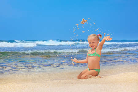 vacationer: Portrait of beautiful little traveler sunbathing on sunny white sand sea beach - happy smiling baby girl has fun. Active travel family lifestyle, water activity and games on summer vacation with child
