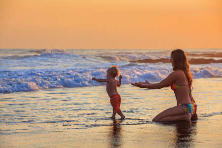 family activities: Family swimming fun in sea beach surf Happy mother, baby son first step - toddler run to ocean wave on sunset sky background Child outdoor activity, parent lifestyle, summer holiday in tropical island
