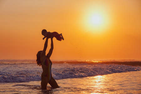air baby: Happy family swimming fun on sea beach - mother tossing up baby son into mid air, catching on sunset sky, sun background Parents outdoor activity, child lifestyle on summer vacation in tropical island