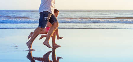 Barefoot legs in action. Happy family fun - parents with baby son running along edge of sea beach surf with sunset light. Active travel lifestyle, water activity and game on summer vacation with child