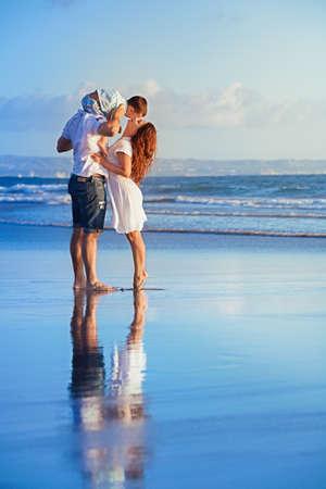 Familia feliz - hijo del bebé en hombros del padre besar a la madre, a pie de diversión a lo largo de surf puesta de sol en la playa de arena negro. los padres y las personas activas actividad al aire libre en las vacaciones de verano con el niño en la isla de Bali